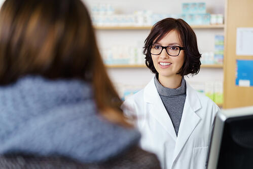 Young Female Pharmacist Talking to a Customer at the Counter Pleasantly.